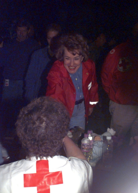 Red Cross President Elizabeth Dole shakes the hand of one of the many volunteers at a shelter located at Grand Forks AFB, North Dakota. The hangers have been housing nearly 3,000 flood victims of the city of Grand Forks. The city was ravaged by flooding and left many homeless. (Substandard image)