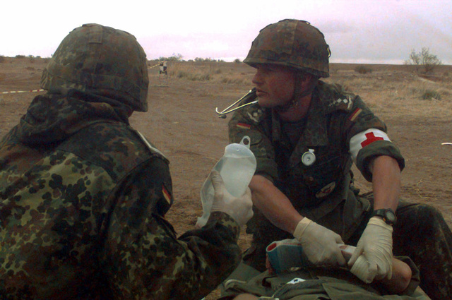 In Dona Ana, Texas, a mass casualty assessment by the German Air Force took place for Roving Sands '97. Here two German medics assess the damage of a simulated casualty from a car wreck victim during ROVING SANDS '97. ROVING SANDS is a multinational effort and is the largest military exercise on United States soil that allows training in a joint environment to hone command and control procedures and integrate new systems in Theater and Air Missile Defense