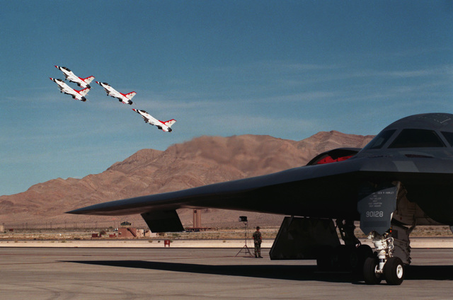A four ship aerial demonstration team, the USAFs Thunder Birds climb afterburners blazing from the Nellis AFB runway just above a parked B-2 Spirit Bomber, during the United States Air Force's 50th Anniversary and Air show