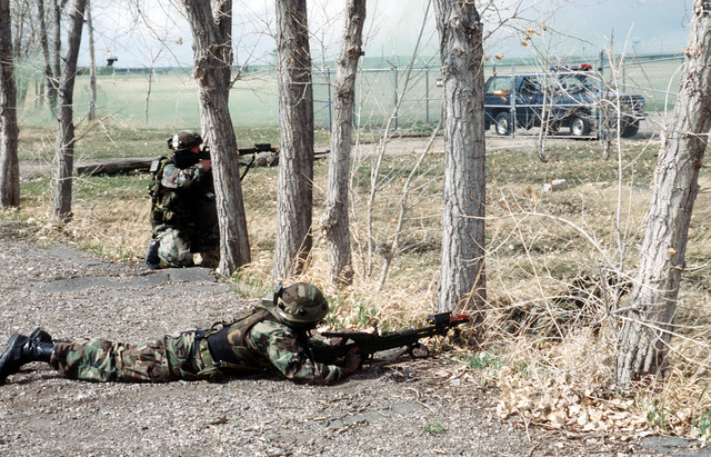 """Engaged in a Launch Facility recapture exercise, STAFF SGT. Marvin Robey, M-60 gunner, AIRMAN 1ST Class Ron Strong and other members of 10th Missile Squadron Security Police, take up positions around the captured launch facilities fence and access road, firing at the last surviving """"bad guys"""" who are hiding inside the launch facility and tenaciously fighting back"""