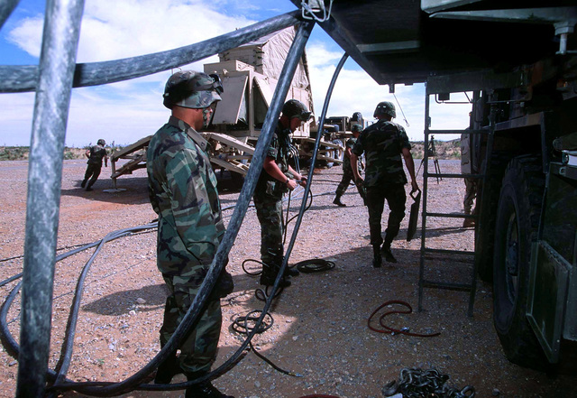 Soldiers assigned to the 11th Brigade, 43rd Air Defense Artillery, from Fort Bliss, Texas, hook up power cables to a mobile generator in preparation for a tactical Patriot missile launch at a site on McGregor Range near El Paso, Texas. The live firings were a real time opportunity for units involved in ROVING SANDS '97 to demonstrate their skills. ROVING SANDS is a multinational effort and is the largest military exercise on United States soil that allows training in a joint environment to hone command and control procedures and integrate new systems in Theater and Air Missile Defense