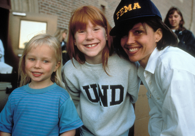 [Severe Storms/Flooding] Grand Forks, ND, May 01, 1997 -  A FEMA official and two children smile for the camera at the Disaster Recovery Center (DRC). FEMA/Michael Rieger