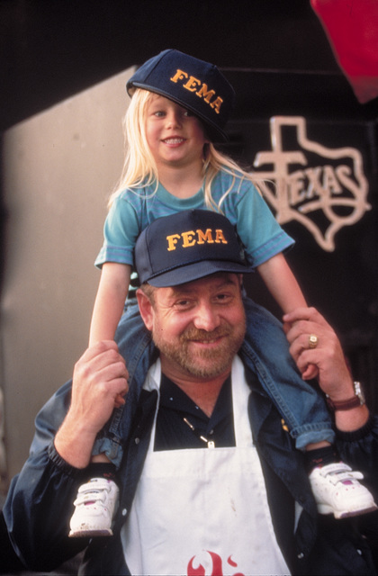 [Severe Storms/Flooding] Grand Forks, ND, May 01, 1997 -  A FEMA official with a child on his shoulders wearing FEMA hats smile for the camera at the Disaster Recovery Center (DRC). FEMA/Michael Rieger