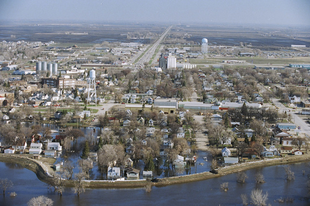 [Severe Storms/Flooding] Grand Forks, ND, May, 1997 -- Aerial view of Grand Forks and the flooded Red River of the North and a levee that was toped with sandbags and breeched, flooding a neighborhood near the river. FEMA/Michael Rieger