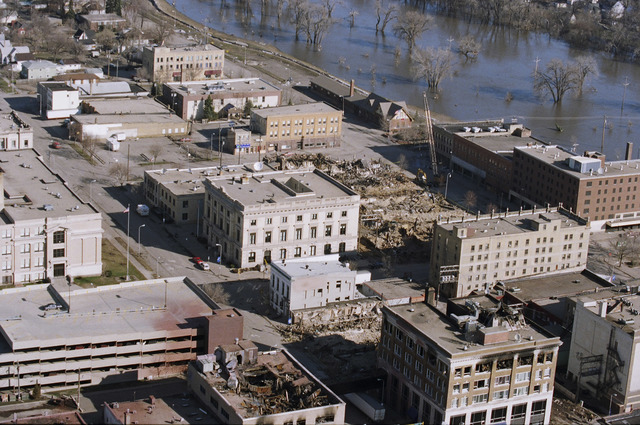 [Severe Storms/Flooding] Grand Forks, ND, May, 1997 -- Aerial view of Grand Forks and the flooded Red River of the North. In the foreground are burned buildings.  FEMA/Michael Rieger