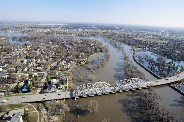 [Severe Storms/Flooding] Grand Forks, ND, May, 1997 -- Aerial view of Grand Forks neighborhood and a bridge crossing the flooded Red River of the North. The levees that were protecting the city are breeched, flooding the area near the river. FEMA/Michael Rieger