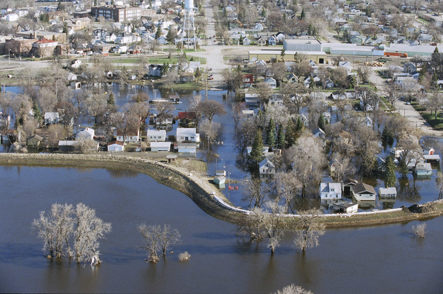 [Severe Storms/Flooding] Grand Forks, ND, May, 1997 -- Aerial view of Grand Forks neighborhood and the flooded Red River of the North. The levee in the foreground was toped with sandbags but breeched, flooding the area near the river. FEMA/Michael Rieger