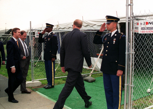 Secretary of Defense William S. Cohen (far left), accompanied by Richard Dooley, Department of Defense (DoD) Project Coordinator at the Pentagon, enters the exhibits at the Public Service Recognition Week held at the National Mall, Washington, DC, May 8,1997. Greeting Secretary Cohen at the gate is Private First Class (PFC) Marc Hudson (left) and PFC James A. Bruhnsen (right). Both are Honor Guard members from E Company, 3rd US Infantry (TOG), Fort Myer, Virginia