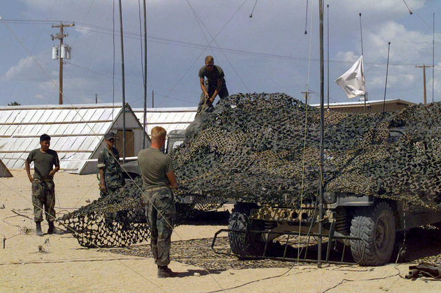 US Marine Corps Air Ground Combat Center (MCAGCC). During Combined Arms Exercise (CAX) 6-97 two High Mobility Multipurpose Wheeled Vehicles (HMMWV) are smartly disguised with camouflage netting by Marines from the Communications Platoon, HQ Company, 6th Marine Regiment, Camp Lejeune, North Carolina