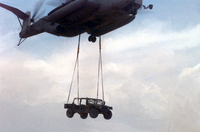 """CH-53E """"Super Stallion"""" Helicopter externally lifts an M998 High-Mobility Multipurpose Wheeled Vehicle (HMMWV) during HST (Helicopter Support Team) training at Observation Post (OP) Crampton during COMBINED RMS Exercise (CX) 6-97. CX 5/6-97 is a MGTF (Marine ir Ground Task Force) exercise being conducted at MCGCC (Marine Corps ir Ground Combat Center), 29 Palms, California. The command element for this exercise is MGTF-6, which is built around the 6th Marine Regiment, 2d Marine Division, Camp Lejeune, North Carolina. Many commands from the II MEF (Marine Expeditionary Force) have sent units to this desert warfare exercise, to fill key billets in the Ground Combat Element (GCE),..."""