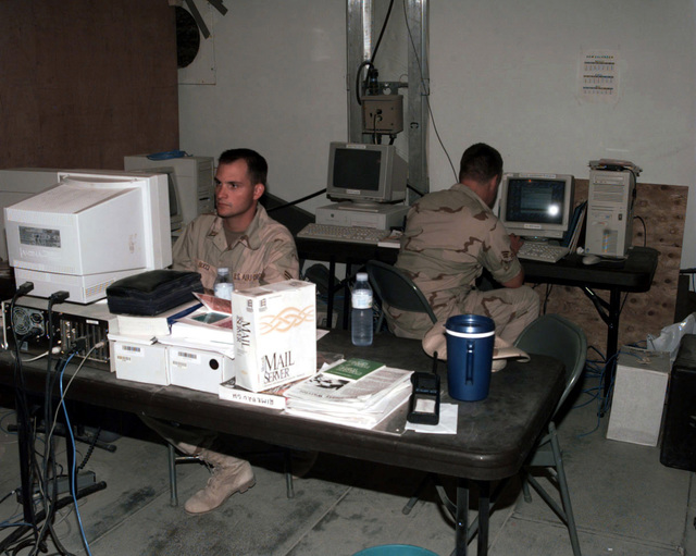 SENIOR AIRMAN (SRA) Ted Bucci (foreground) and SRA Steve Summerlin, both from Seymour Johnson Air Force Base Communications Squadron LAN shop, keep the lines of communication open by making sure the E-mail server is not clogged up. The airmen as part of Air Expeditionary Force (AEF) IV are in country in support of Operation SOUTHERN WATCH. SOUTHERN WATCH enforces the United Nations Security Council Resolution 688 that establishes a no-fly zone over Southern Iraq below the 32nd parallel