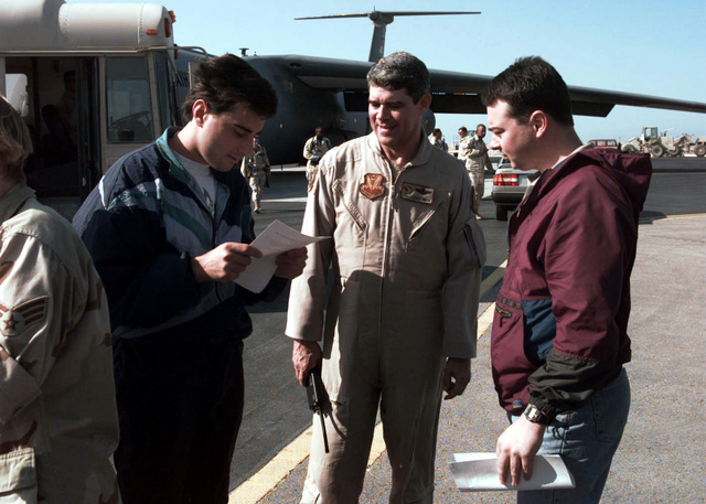 Newscasters Dallas Woodhouse (left) and Jim Johnson of WNCN channel 17 out of Raleigh, North Carolina, go over their 3 day itinerary with Brigadier General Lance Smith, Commander 4TH Air Expeditionary Wing during Operation SOUTHERN WATCH. SOUTHERN WATCH enforces the United Nations Security Council Resolution 688 that establishes a no-fly zone over Southern Iraq below the 32nd parallel