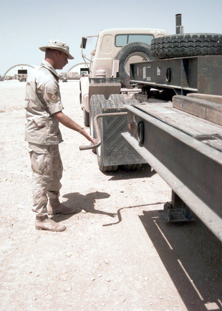 Technical Sergeant Stewart of Seymour Johnson AFB, North Carolina, Transportation Squadron, cranks down the landing/ stabilizing gears to the trailer of an 18 wheeler during Operation SOUTHERN WATCH. SOUTHERN WATCH enforces the United Nations Security Council Resolution 688 that establishes a no-fly zone over Southern Iraq below the 32nd parallel