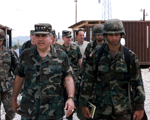 United States Army General George A. Joulwan (left), Supreme Allied Commander, Europe (SACEUR) and Commaner-in-CHIEF, United States European Command, walks alongside his nephew, Private First Class (PFC) Chernov (right), Alpha Company, Task Force 1-13 (1ST Battalion, 13th Armor, 3rd Brigade, 1ST Armored Division), Quick Reaction Force, as they walk toward the recreation center to commend the soldiers of Task Force 1-41 (1ST Battalion, 41st Infatry, 3rd Brigade, Ist Armored Division) on how much their hard work is appreciated during Operation JOINT GUARD. Camp Dobol, Bosnia-Herzegovina, 23 May 1997