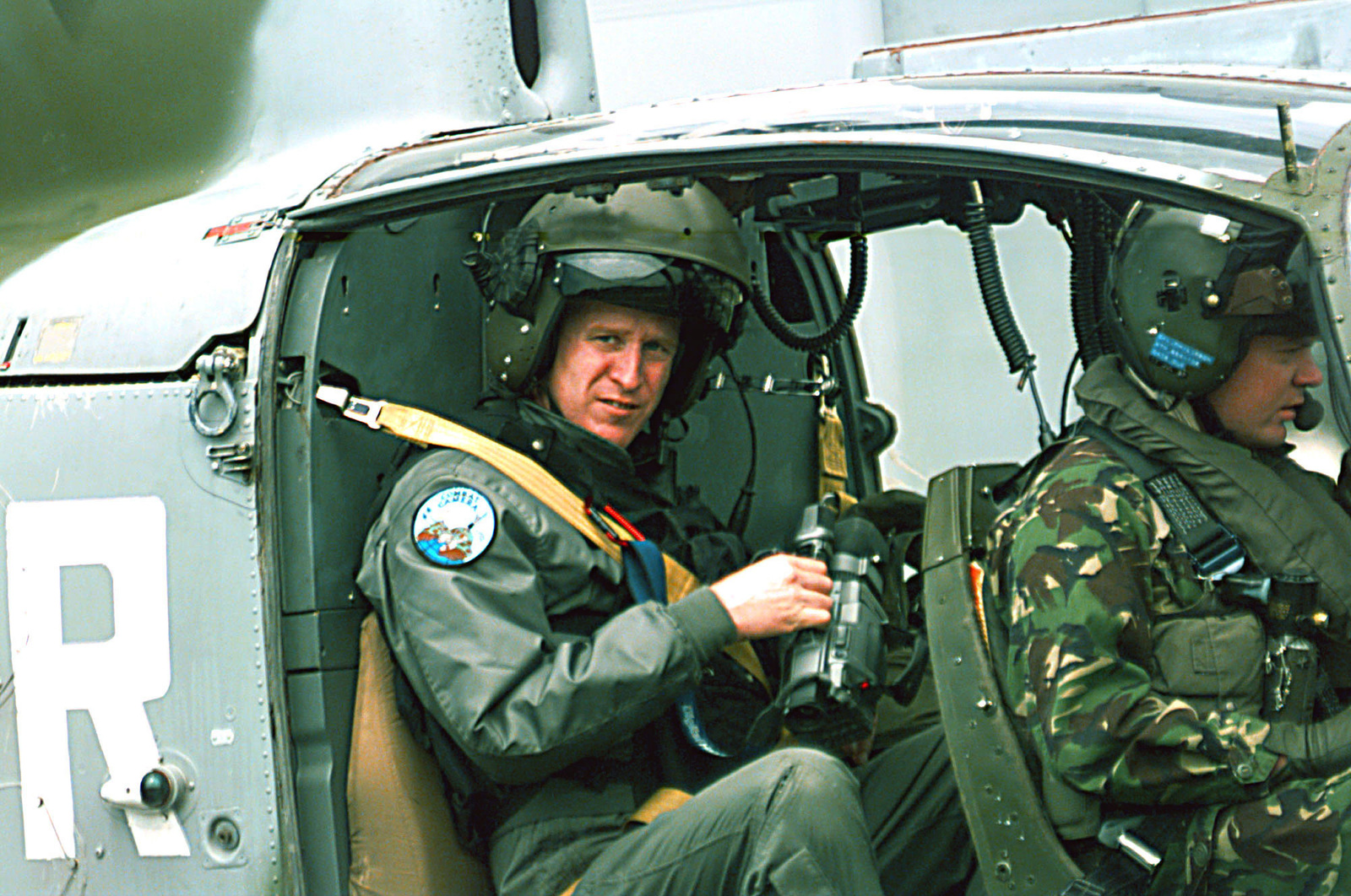 TSGT Jeffrey Chrisholm a videographer from the 1ST Combat Camera Squadron, Charleston Air Force Base, South Carolina, prepares for an aerial reconnaissance mission seated in a British Army SA-341 Gazelle helicopter