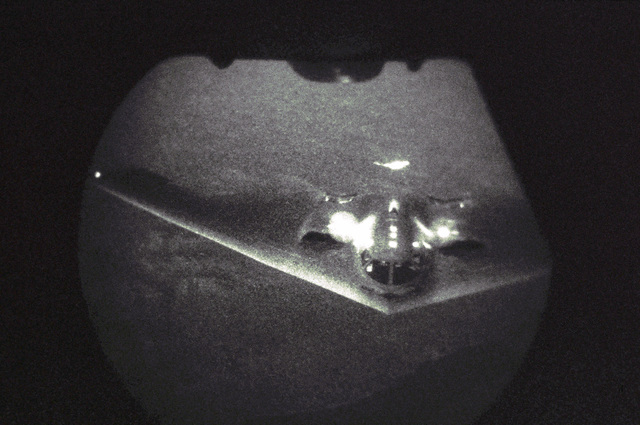 Low light level, fish-eye lens view, showing A US Air Force (USAF) B-2 Spirit aircraft approaching a USAF KC-10 Extender aircraft during a nighttime refueling mission