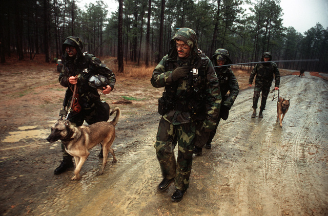 """Security police K-9 units from the 314th Airlift Wing, Little Rock Air Force Base, Arkansas, patrol the muddy roads at the Joint Readiness Training Center (JRTC). The troops participating in Air Warrior II were constantly on the lookout for """"enemy"""" forces in the area during the exercise conducted in February 1997.Exact Date Shot UnknownPublished in AIRMAN Magazine June 1997"""