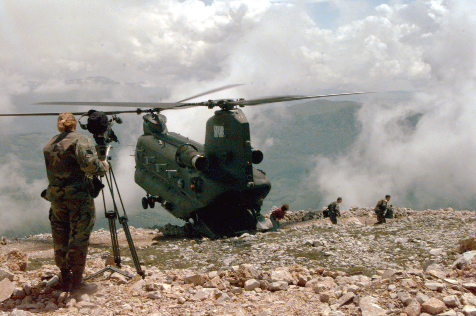 SRA Heather Odom, videographer from the 1ST Combat Camera Squadron, Charleston Air Force Base, South Carolina using her Sony VX-1000 camera documents, through the rotor wash, the landing of a British CH-47 helicopter on the top of Mt. Lisin