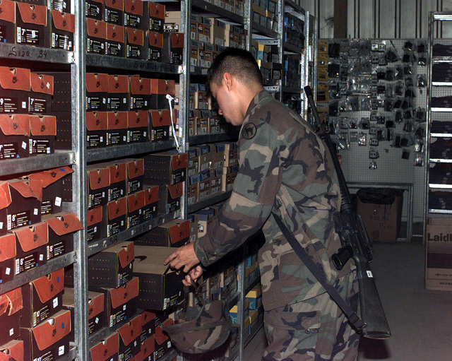 US Army, Private First Class (PFC) Gonzalez, 678th Personnel Service Detachment, carrying a 5.56 mm M16 rifle, checks out the wide variety of running shoes offered to the soldiers of Task Force Eagle, while shopping at the Base Exchange. Operation JOINT GUARD, Tuzla Air Base, Bosnia-Herzegovina, 9 June 1997