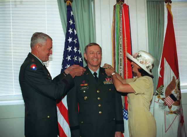 GEN Dennis J. Reimer, Army CHIEF of STAFF (left), pins lieutenant general stars on David K. Heebner, Assistant Vice CHIEF of STAFF, U.S. Army. General Reimer is assisted by LGEN Heebner's wife, Bonnie, during the promotion ceremony