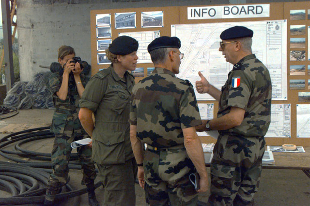 French LGEN Philippe Mansuy, Deputy Commander of the Stabilization Force (SFOR) is briefed on the status of the Butmir Compound by Canadian CPT Jane Thelwell of the 1ST Construction Engineer Unit, (1CEU). A1C Michelle Leonard, still photographer with the 1ST Combat Camera Squadron, Charleston Air Force Base, South Carolina, documents their discussion. The Compound will house Stabilization Force (SFOR) troops who are currently living in Zetra, Parliament and Residency Compounds. SCREEN RESOLUTION ONLY