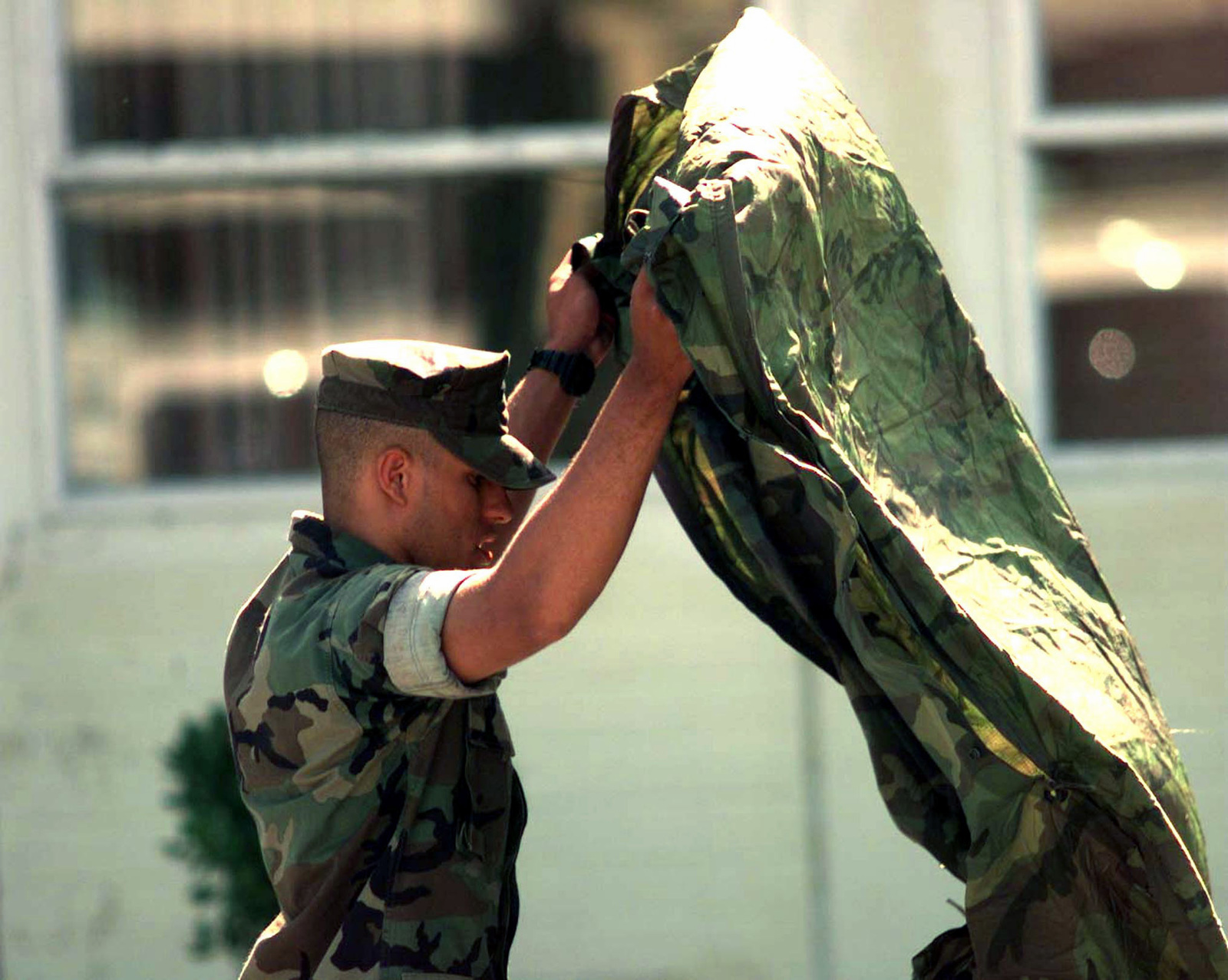 A Marine from first Marine Regiment HQ Company shakes the dirt from his poncho liner prior to reporting in from Camp Horner, Camp Pendleton, to USS MOUNT VERNON (LSD 39) which is participating in Exercise KERNEL BLITZ '97 off coast of Southern California. KERNEL BLITZ is a bi-annual Commander-in-CHIEF Pacific (CINCPAC) fleet training exercise (FLEETEX) focused on operational/tactical training of Commander, Third Fleet (C3F)/ I Marine Expeditionary Forces (MEF) and Commander, Amphibious Group 3 (CPG-3)/ 1ST Marine Division (MARDIV). KERNEL BLITZ is designed to enhance the training of Sailors and Marines in the complexities of brigade-size amphibious assault operations