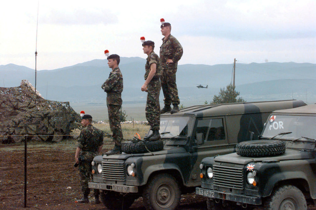 Stabilization Force (SFOR) British VIP's, with distinctive hat ornaments that symbolizes their VIP status, watch the British Warrior armored fighting vehicles during the live fire exercise by standing on their vehicles