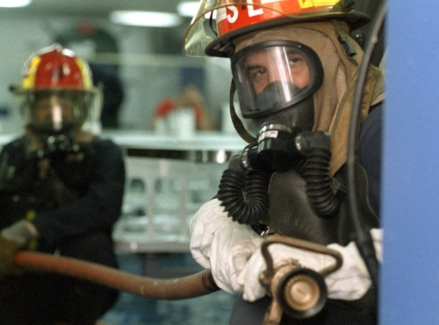 PETTY Officer Third Class (DC3) Scott Ferreira keeps watch over a possible explosive device during a drill onboard the USS TARAWA (LHA 1) during Exercise KERNEL BLITZ '97. Firefighters are seen with Self Contained Breathing Apparatus (SCBA) wearing a Navy Firefighter Helmet with face shield and head lamp. KERNEL BLITZ is taking place off the coast of Southern California to train Navy and Marine Corps personnel in amphibious operations