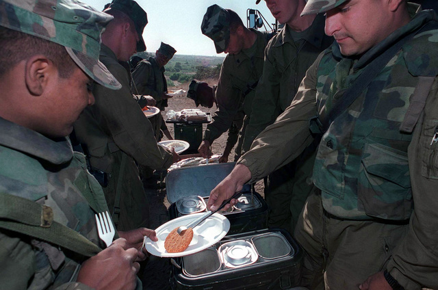 Sergeant Marcos Enriquez (Right), D Co, 3d Amphibious Assault Battalion, 1ST Marine Division, serves hot chow to Opposition Force Marines, also from 3d AABn, at Camp Pendleton, California, during Exercise KERNEL BLITZ '97. KERNEL BLITZ is a bi-annual Commander-in-CHIEF Pacific (CINCPAC) fleet training exercise (FLEETEX) focused on operational/tactical training of Commander, Third Fleet (C3F)/ I Marine Expeditionary Forces (MEF) and Commander, Amphibious Group 3 (CPG-3)/ 1ST Marine Division (MARDIV). KERNEL BLITZ is designed to enhance the training of Sailors and Marines in the complexities of brigade-size amphibious assault operations