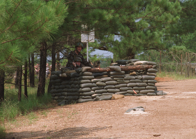 Soldiers take cover behind sandbags, at an unknown checkpoint, at the Joint Readiness Training Center