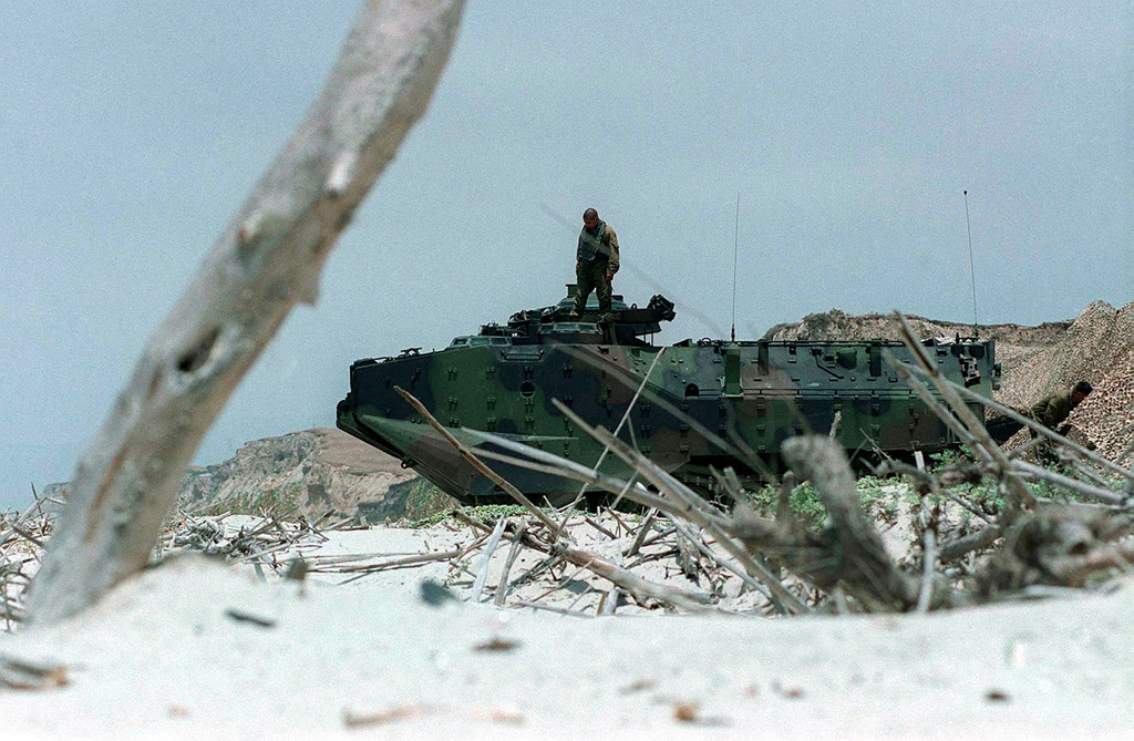 """Lance Corporal Alexander T. Acocello, from Mobility Counter Mobility Platoon, Headquarters & Service Company, 3d Amphibious Assault Battalion, 1ST Marine Division, prepares his Amphibious Assault Vehicle (AAV-7A1) for a """"splash"""" at White Beach during Exercise KERNEL BLITZ '97. KERNEL BLITZ is a bi-annual Commander-in-CHIEF Pacific (CINCPAC) fleet training exercise (FLEETEX) focused on operational/tactical training of Commander, Third Fleet (C3F)/ I Marine Expeditionary Forces (MEF) and Commander, Amphibious Group 3 (CPG-3)/ 1ST Marine Division (MARDIV). KERNEL BLITZ is designed to enhance the training of Sailors and Marines in the complexities of brigade-size amphibious assault operations"""