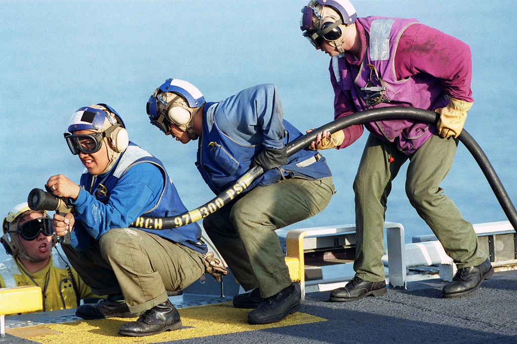 Sailors practice their fire-fighting skills during a flight deck fire drill onboard USS TARAWA (LHA 1) as part of Exercise Kernel Blitz '97. Personnel in jerseys colored red are crash/salvage, ordnance; in yellow are aircraft handlers; in blue are plane handlers, elevator operators, messenger, chocks and chains, tractor drivers. KERNEL BLITZ is designed to enhance the training of Sailors and Marines in the complexities of brigade-size amphibious assault operations