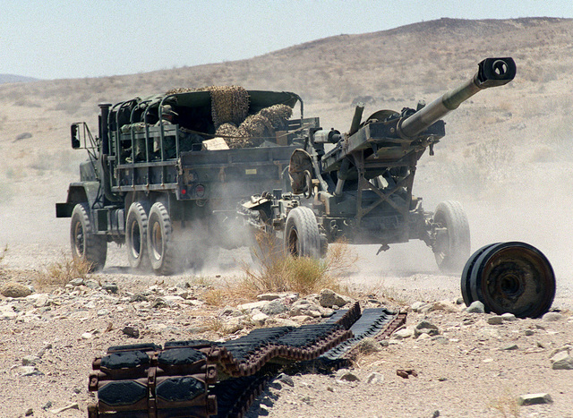 Marines in a M925A2 5-ton cargo truck from Alpha Battery, Camp Pendleton, California, pull a M198 155mm Medium Howitzer, Towed to its firing position to support the Supporting Arms Coordination Exercise (SACEX) portion of Exercise KERNEL BLITZ '97 at Marine Corps Air Ground Combat Center (MCAGCC) 29 Palms. KERNEL BLITZ is designed to enhance the training of Sailors and Marines in the complexities of brigade-size amphibious assault operations