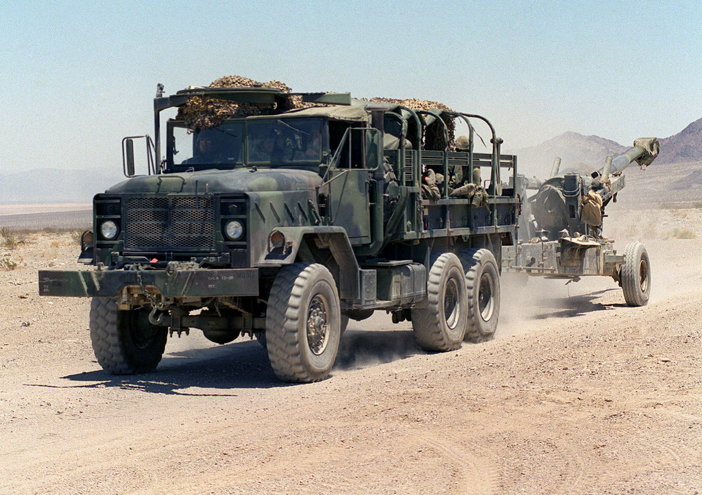 Marines use an M925A2 5-ton cargo truck from Alpha Battery, Camp Pendleton, California, to tow an M198 155mm Medium Howitzer to its firing position to support the Supporting Arms Coordination Exercise (SACEX) portion of Exercise KERNEL BLITZ '97 at Marine Corps Air Ground Combat Center (MCAGCC) 29 Palms. KERNEL BLITZ is designed to enhance the training of Sailors and Marines in the complexities of brigade-size amphibious assault operations