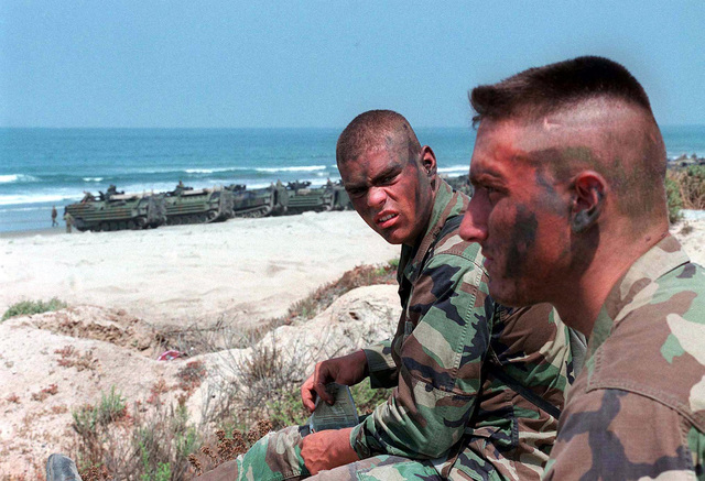 Private First Class (PFC) Jeff A. Troxel (facing camera) and PFC Nathan J. Haines prepare to eat noon chow at white beach on Camp Pendleton during work-ups for Exercise KERNEL BLITZ '97. Amphibious Assault Vehicles (AAV-7A1) are seen in background. KERNEL BLITZ is a bi-annual Commander-in-CHIEF Pacific (CINCPAC) fleet training exercise (FLEETEX) focused on operational/tactical training of Commander, Third Fleet (C3F)/ I Marine Expeditionary Forces (MEF) and Commander, Amphibious Group 3 (CPG-3)/ 1ST Marine Division (MARDIV). KERNEL BLITZ is designed to enhance the training of Sailors and Marines in the complexities of brigade-size amphibious assault operations