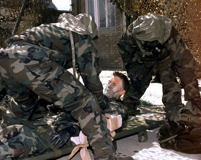 US Army medics, wearing the M40A1 Chemical-Biological Mask, from the 61st Area Support Medical Battalion perform first aid on a chemically contaminated soldier. This was part of a decontamination exercise performed at a coal mine in the town of Lukavac, Bosnia-Herzegovina. Operation JOINT GUARD, 27 June 1997