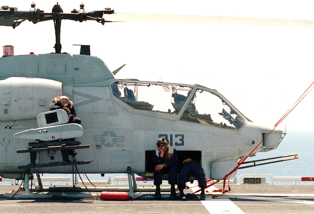 Flight deck personnel aboard USS TARAWA (LHA 1) take a break on an Marine AH-1W Super Cobra between flight quarters during Exercise KERNEL BLITZ '97. KERNEL BLITZ is designed to enhance the training of Sailors and Marines in the complexities of brigade-size amphibious assault operations