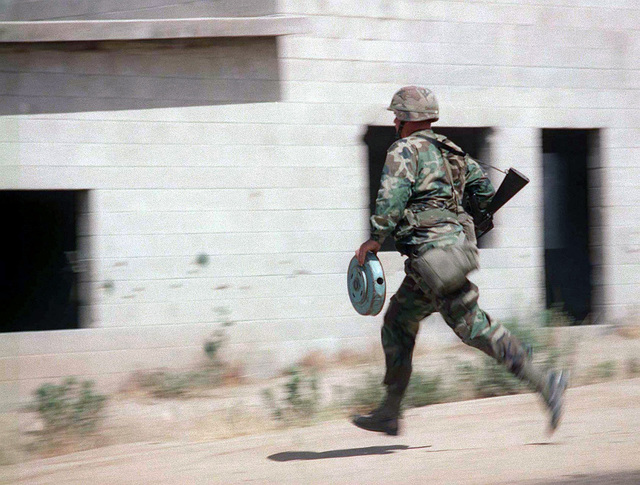 An Army reservist infantryman simulates throwing a bomb into a building where the enemy forces are located during Exercise KERNEL BLITZ '97. KERNEL BLITZ is a bi-annual Commander-in-CHIEF Pacific (CINCPAC) fleet training exercise (FLEETEX) focused on operational/tactical training of Commander, Third Fleet (C3F)/ I Marine Expeditionary Forces (MEF) and Commander, Amphibious Group 3 (CPG-3)/ 1ST Marine Division (MARDIV). KERNEL BLITZ is designed to enhance the training of Sailors and Marines in the complexities of brigade-size amphibious assault operations