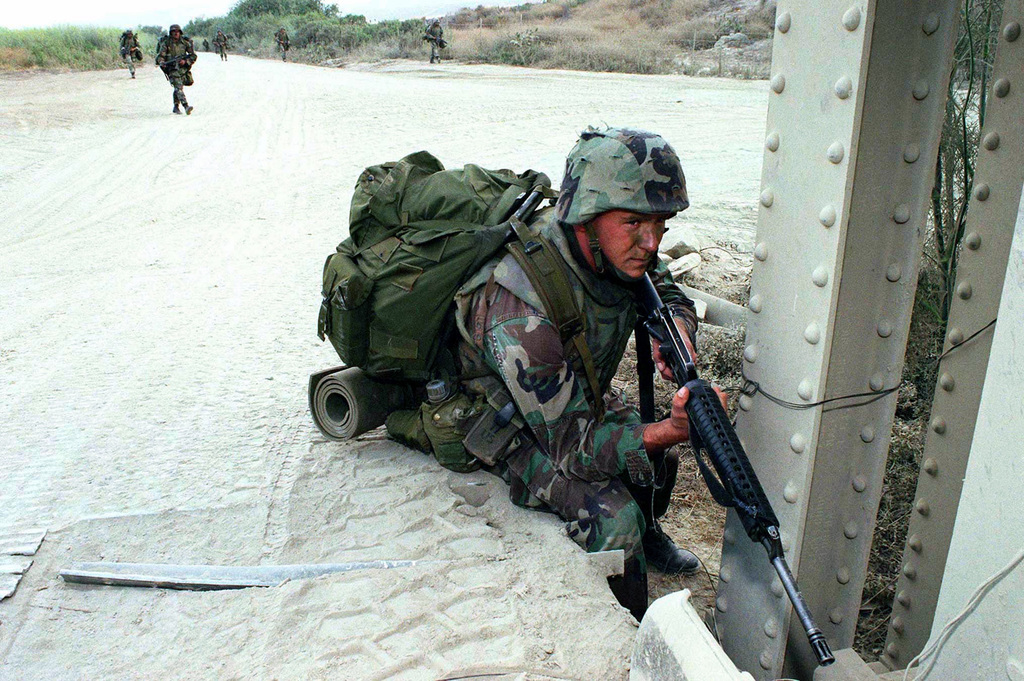 Lance Corporal Jeff Schultz, Battalion Landing Team 11, posts a watch along a bridge as his team passes through on a roving patrol during Exercise KERNEL BLITZ '97. He's armed with Colt M16A2 5.56mm Rifle and carries his gear in an All-purpose Lightweight Individual Carrying Equipment (ALICE) pack. KERNEL BLITZ, largely taking place off the coast of Southern California and Camp Pendleton, is designed to enhance the training of Sailors and Marines in the complexities of brigade-size amphibious assault operations