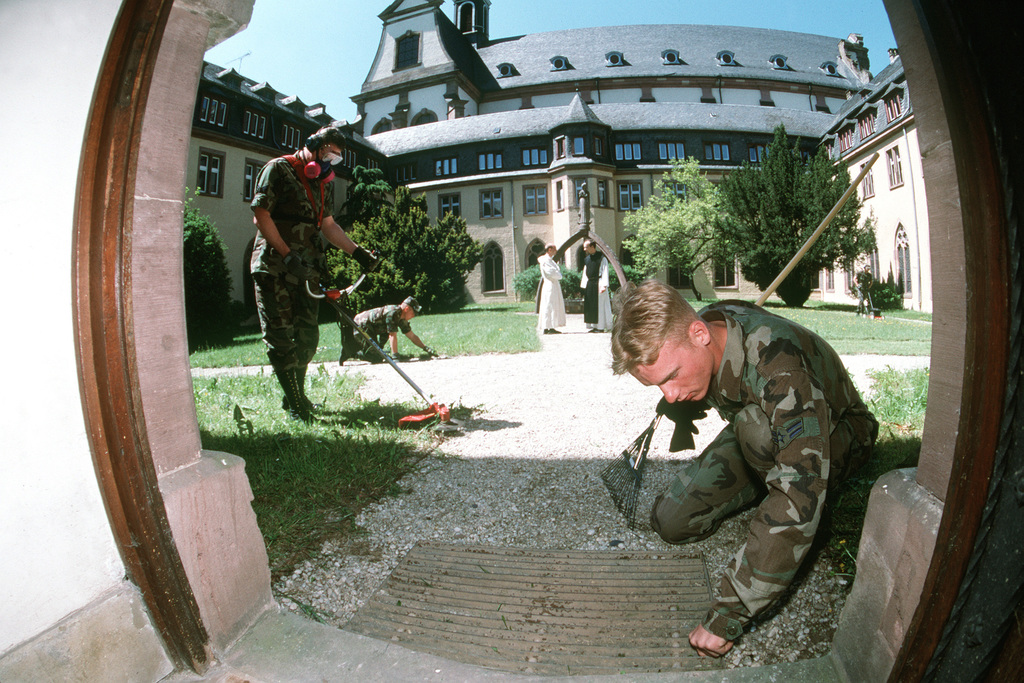AIRMAN 1ST Class Roger Sindecuse pulls weeds from the courtyard of Himmerod Abbey, an 11th century religious retreat near Spangdahlen Air Base, Germany. AIRMAN Sindecuse and other 52nd Equipment Maintenance Squadron members from Spangdahlem voluntarily maintain the grounds of the 8-year-old church.Exact Date Shot Unknown. Published in AIRMAN Magazine October 1997