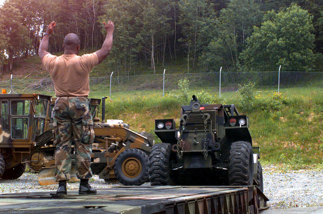 Cororal D. L. Countee, ground guides a DTC 4000 ound forklift (Extended Boom Forklift (EBFL)), onto a M870A1 trailer, at the Bjugn Cave facility. Countees' arent command is 2D Force Service Suort Grou (FSSG) but he is currently attached to the Norway Air-Landed Marine Exeditionary Brigade/Offload Prearation Party, (NALMEB/OPP), II Marine Exeditionary Force, Forward, (II MEF FWD). This item is being reared for shiment to Estonia, for use in BALTIC CHALLENGE 97, a Partnershi for Peace (PfP) exercise. The US Marine Cors has equiment stored in Norway, as art of the NALMEB Preositioning Program. The NALMEB rogram contains equiment and 30 days of sulies to suort a 13,000...