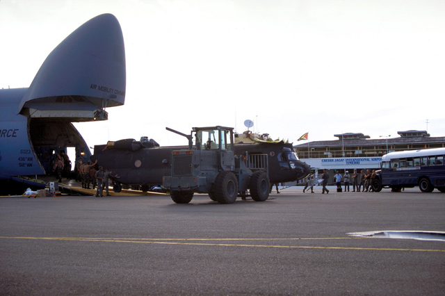 An Army National Guard CH-47D Chinook helicopter from Detachment 1, Company F, 106th Aviation Davenport, Iowa is unloaded from a C-5B Galaxy airlifter at Cheddi Jagan International Airport, Timehri, Guyana. The C-5B is from 3rd Airlift Squadron, 436th Airlift Wing, Dover Air Force Base, Delaware and is supporting New Horizon '97, the first combined humanitarian and civic assistance exercise conducted between the United States and Guyana. A 10K forklift is in the foreground partially blocking view of Chinook. Military personnel from the Air Force, Air Force Reserve & National Guard, Army, Army National Guard and Marine Corps participated in the exercise which included engineering and ...