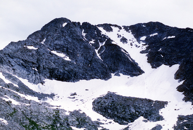 An overall view of the A-10 crash site near the summit of Gold Dust Peak. The snow covered area just above and to the left of center is the main debris site