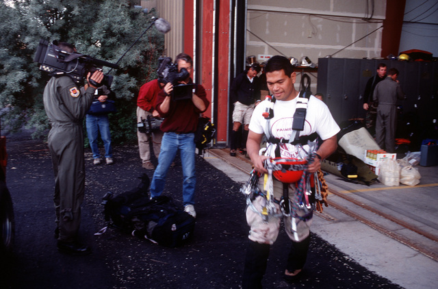 Members of the military and civilian media with video cameras document the necessary preparations required before ascending to the A-10 crash site near Gold Dust Peak by pararescuemen like SSGT Ishmael Antonio (right) who is assigned to 58th Special Operations Wing, Kirtland Air Force Base, New Mexico