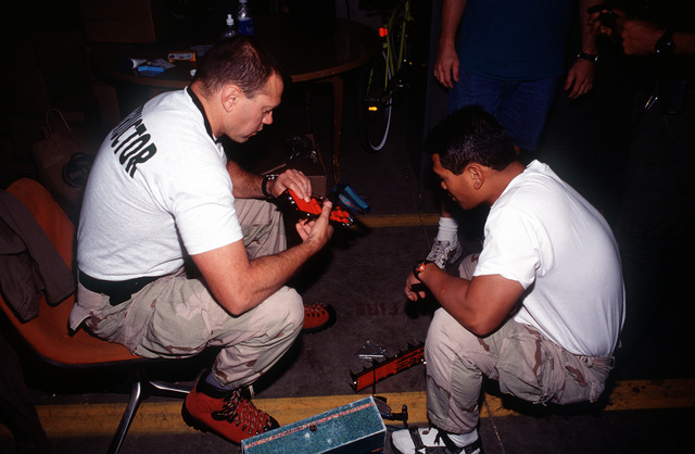 SMSGT Paul Miller (left) and SSGT Ishmael Antonio (right), assigned to 58th Special Operations Wing, Kirtland Air Force Base, New Mexico, check out their equipment prior to ascending to the A-10 crash site near Gold Dust Peak