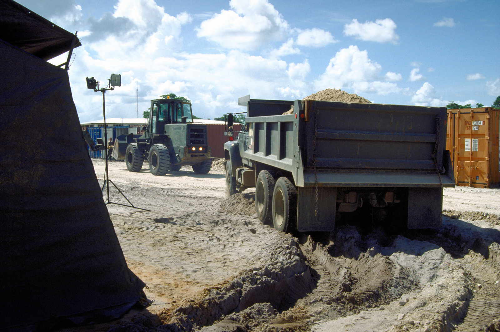 A front end loader helps tow one of the 820th Red Horse Squadron's large dump truck out of the wet sand in Camp Stephenson's tent city. The tent city will provide housing for the Combined Task Force Falcon participants in New Horizon '97, the first combined humanitarian and civic assistance exercise conducted between the United States and Guyana. Military personnel from the Air Force, Air Force Reserve & National Guard, Army, Army National Guard and Marine Corps participated in the exercise which included engineering and medical readiness training