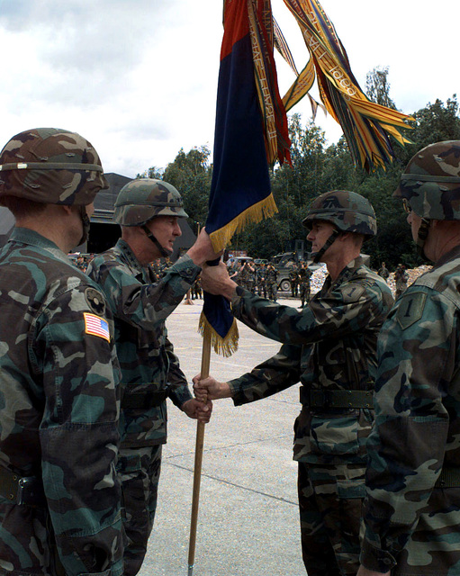 US Army, General William W. Crouch (left), Commander United States Army, Europe, 7th Army and Stablization Force (SFOR), transfers the flag to the new Commander of Multi-National Division North, Task Force Eagle and 1ST Infantry Division, Major General David L. Grange, USA, during the Transfer of Authority ceremony. Departing commander, MG Montgomery C. Meigs, USA, is in left foreground and 1ST INF DIV Sergeant Major Harold Montgomery, USA, is in right foreground. Operation JOINT GUARD, Eagle Base, Tuzla, Bosnia and Herzegovina, on 9 July 1997