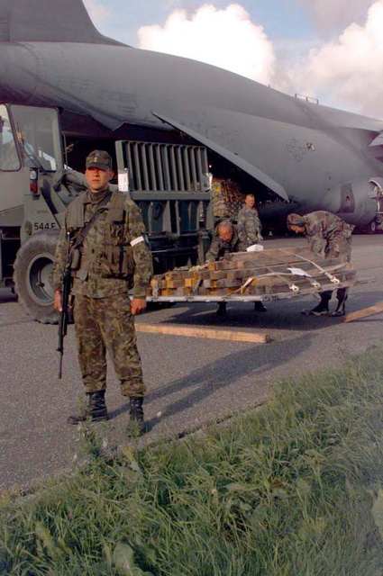 An Estonian soldier provides security while an US Air Force C-5 Galaxy unloads Marine Corps equipment and supplies at the airport. The multinational exercise is conducted in the spirit of NATO's Partnership for Peace (PfP) initative. More than 2600 military personnel from Denmark, Estonia, Finland, Latvia, Lithuania, Norway, Sweden, and the USA will participate in the second PfP land exercise conducted in the Baltic region. While this exercise will conduct training along peacekeeping/humanitarian assistance mission standards, significant US Navy and Marine Corps capabilities never exercised in Europe will be performed including the use of equipment from the US Marine Corps Norway ...