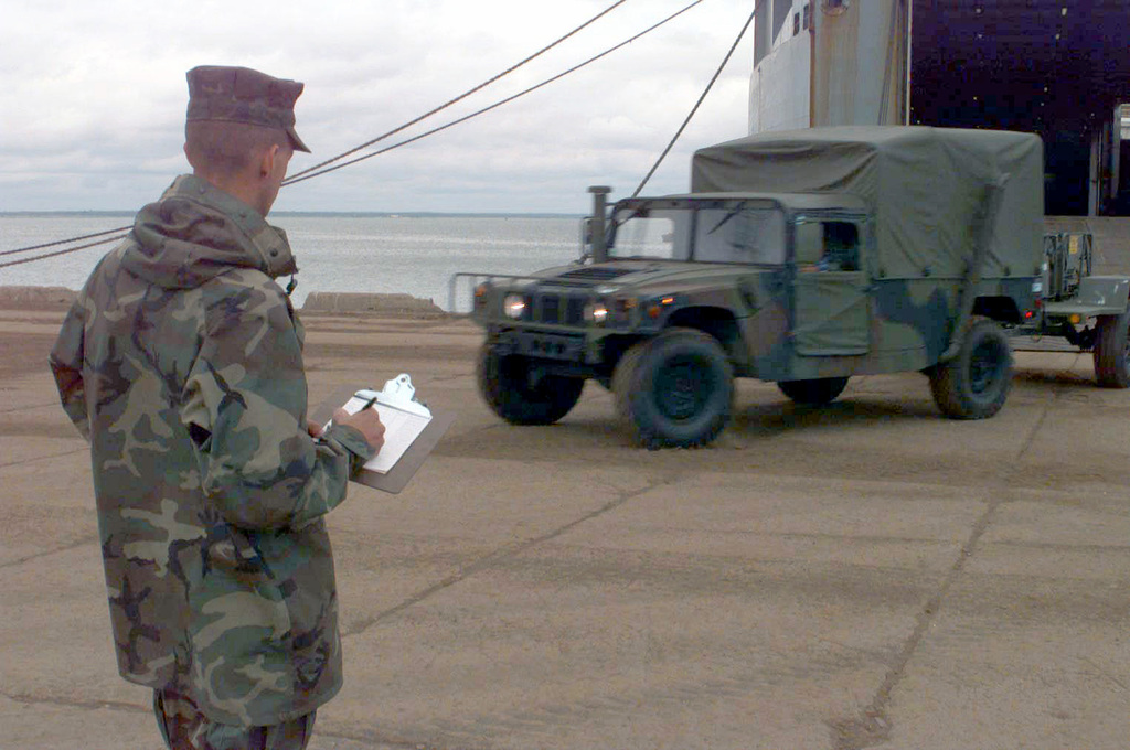 """Lance Corporal . B. Baldwin checks off serial numbers of vehicles being offloaded from the MV Villars, at the port facility in Paldiski, stonia. The Villars had brought equipment stored in Norway under the Norway Air-Landed Marine xpeditionary Brigade (NALMB) program to stonia for BALTIC CHALLNG '97. BALTIC CHALLNG is a multinational exercise conducted in the spirit of NATO's Partnership for Peace (PfP) initiative. More than 2600 military personnel from Denmark, stonia, Finland, Latvia, Lithuania, Norway, Sweden, and the US, will participate in the second """"in the spirit of PfP"""" land exercises conducted in the Baltic region. Co-Commanders for the exercise being held in Paldiski,..."""