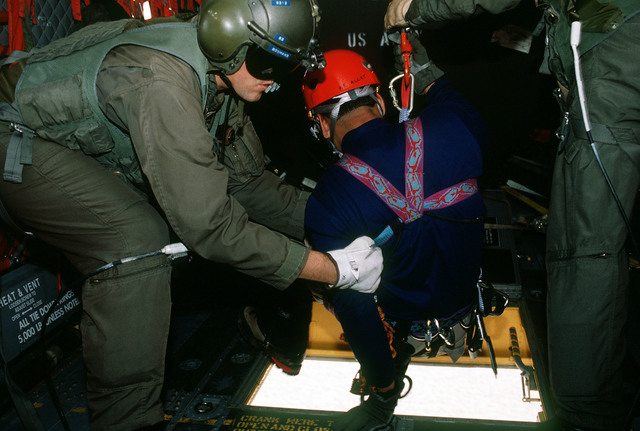 Pararescuemen SSGT Ishmael Antonio (center), assigned to the 58th Special Operations Wing, Kirtland Air Force Base, New Mexico, is assisted through the floor opening of a CH-47 helicopter by one of the crewmembers just prior to being lowered to the A-10 crash site. The CH-47, which increases productivity of the A-10 recovery effort, belongs to Detachment 1, Company G, 140th Aviation, Nevada Army National Guard